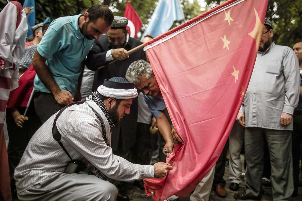 Uyghur protesters burn a Chinese flag in Istanbul, where some have settled after fleeing their homeland.