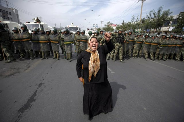 A Uyghur sister protests the heavy-handedness of the Chinese security forces.