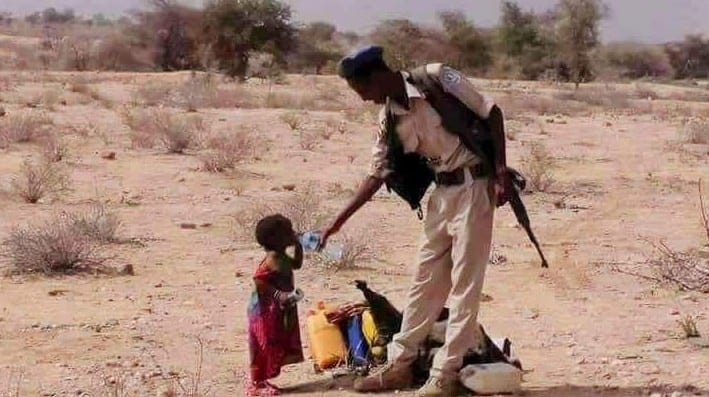 A man giving water to a thirsty child in Somalia