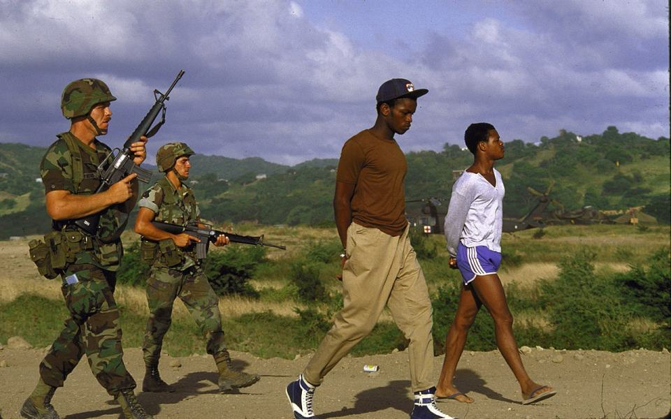 U.S. troops guarding suspected members of the People's Revolutionary Army of Grenada during the Urgent Fury invasion of the island after a Marxist coup.